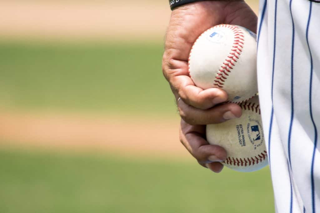man holding baseballs