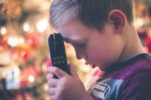 boy praying with Bible